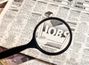Magnifying glass searching job listings in the newspaper