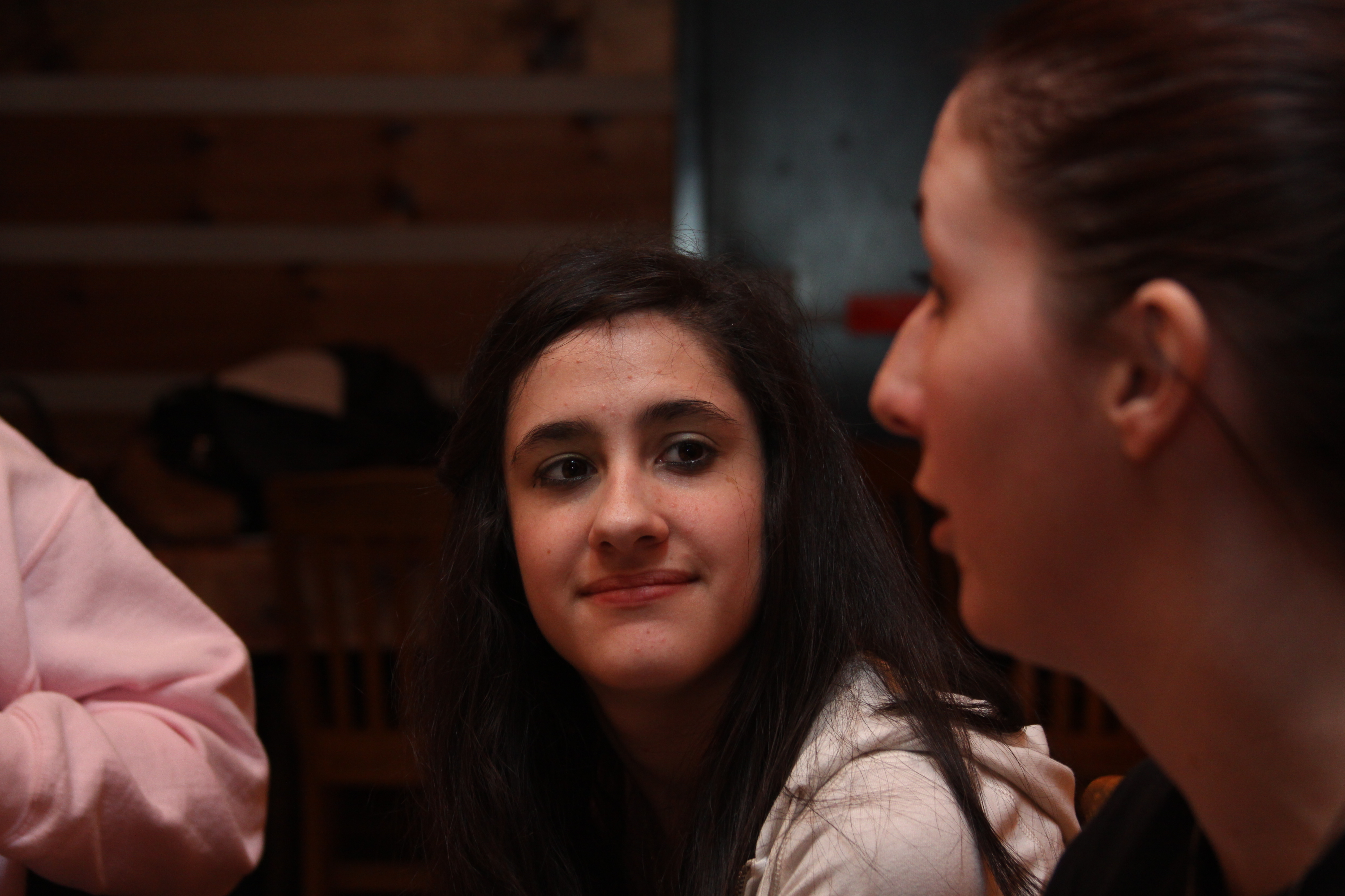 Picture of a teen girl smiling and listening to conversation at an IMAGE teen event.
