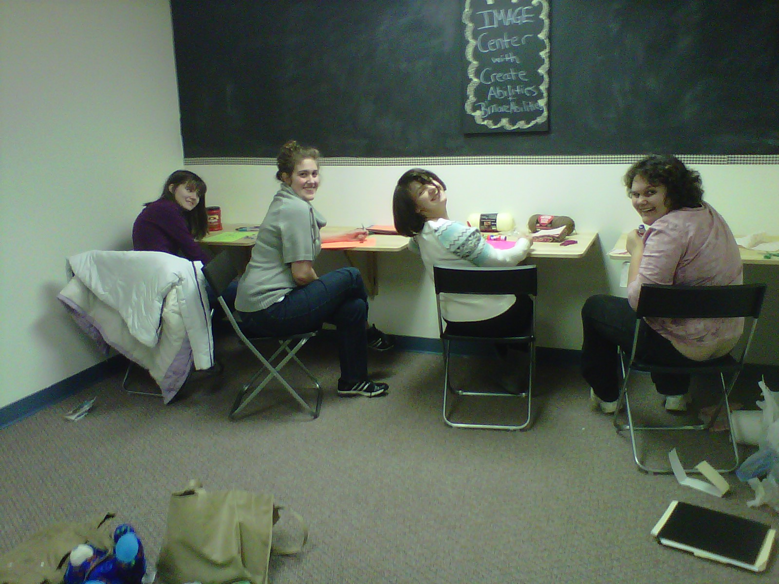 Four teen girls crafting self-portraits during a Girls Night Out session.