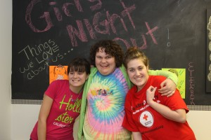 Three teen girls hugging and smiling at Girls Night Out in Harford County.