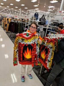 Participant holding up an ugly sweater