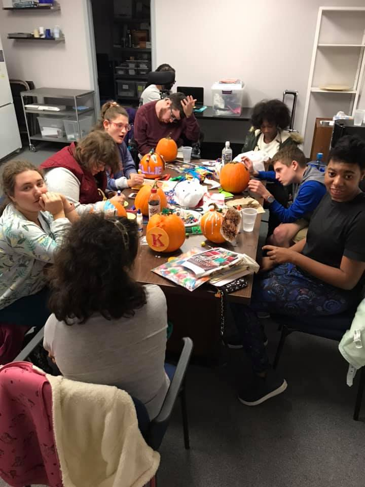 A group of kids carving pumpkins
