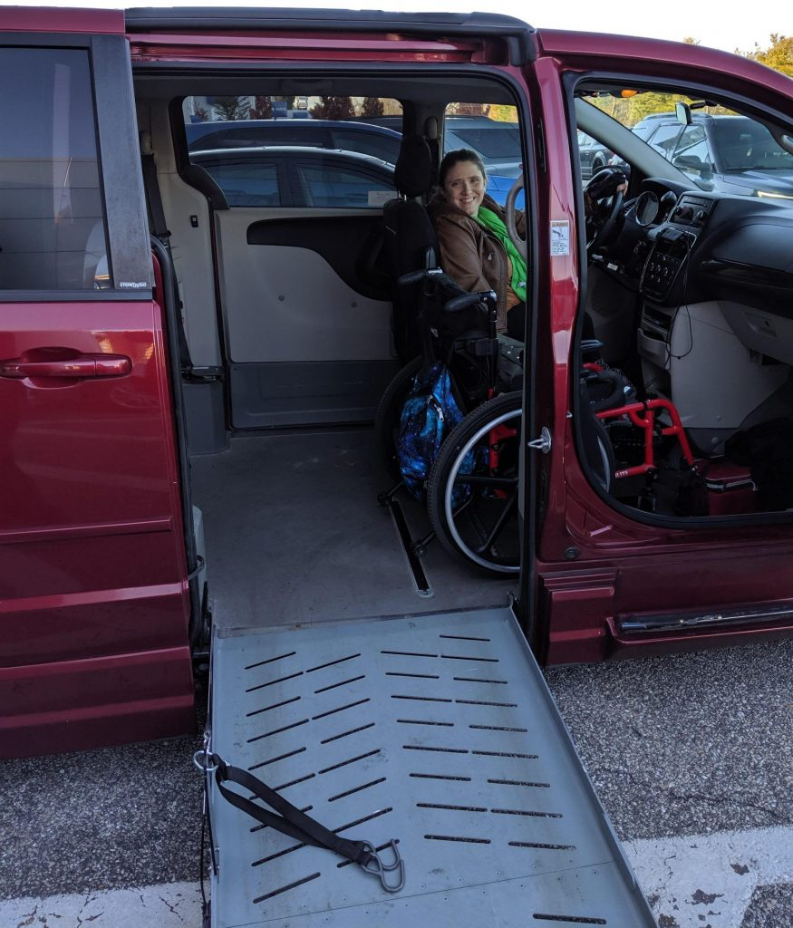 A young woman drives a wheelchair accessible van, her wheelchair parked beside her