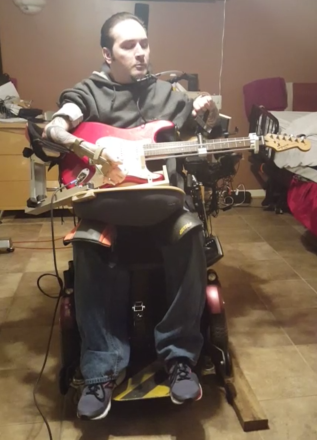 Rock and Roll artist playing modified guitar