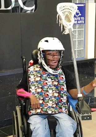 Kid using a wheelchair adapted so he can play lacrosse