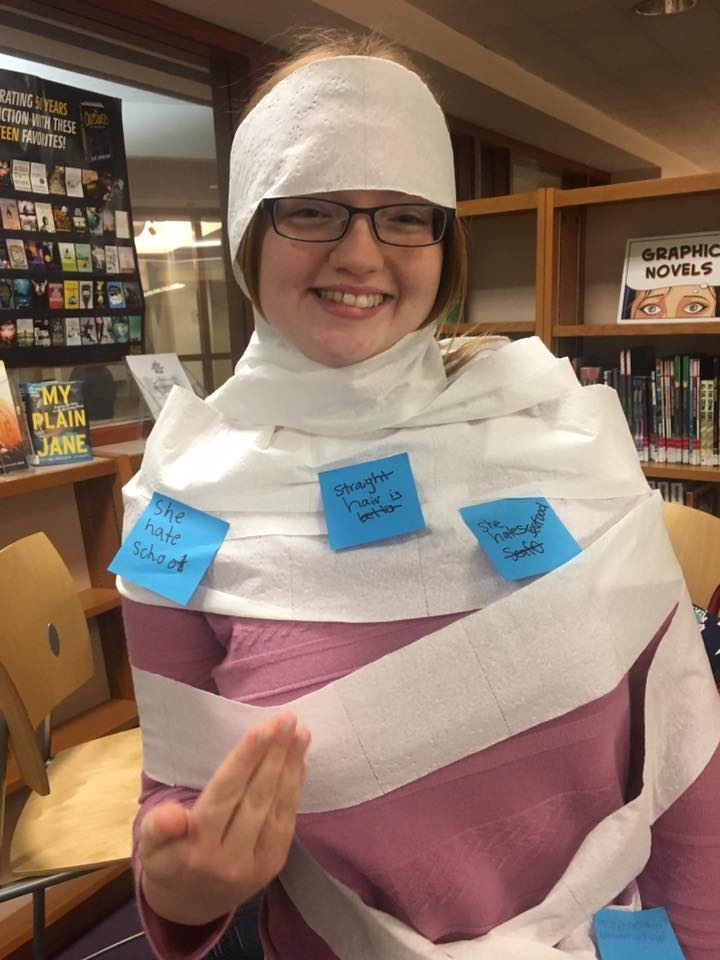 Girl in the library wrapped in toilet paper covered in post-it notes