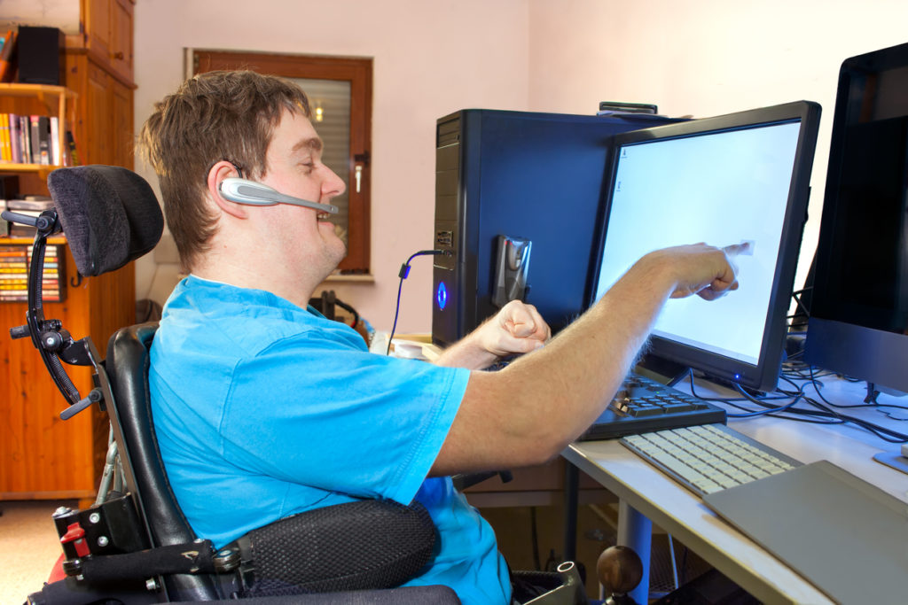 Man with infantile cerebral palsy using a computer.