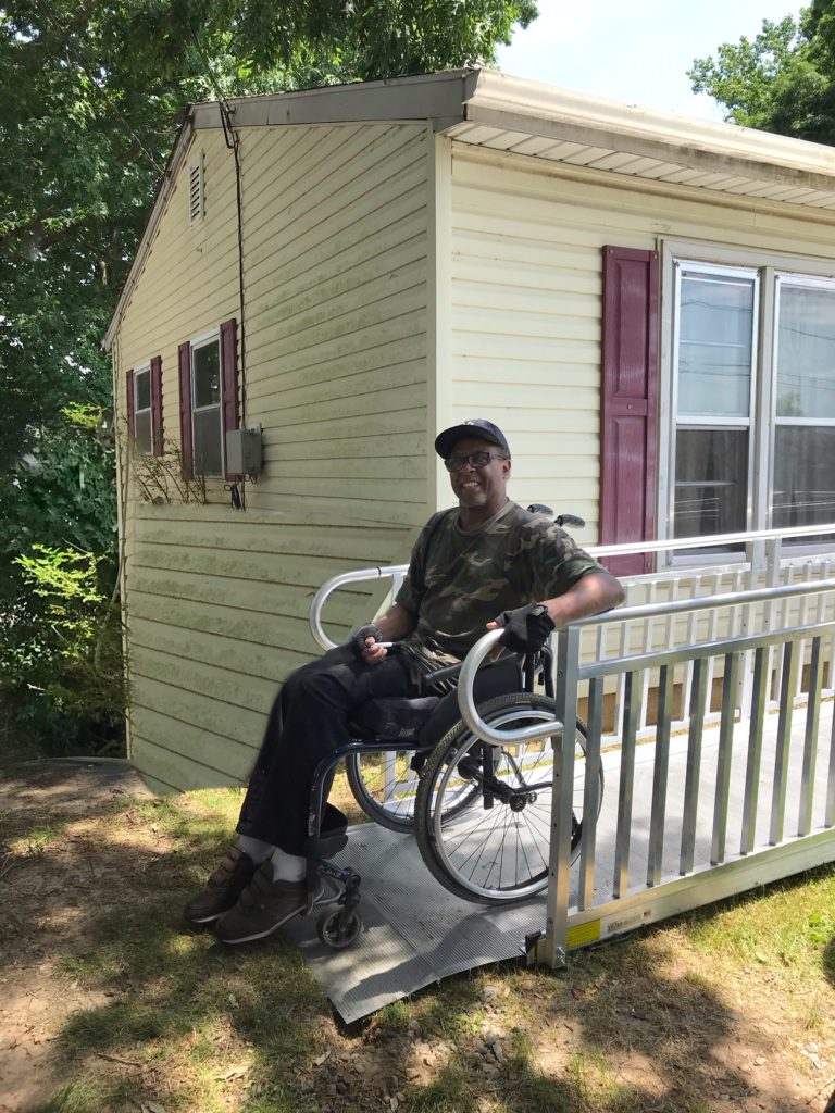 a man uses a ramp to get his wheelchair out of the house