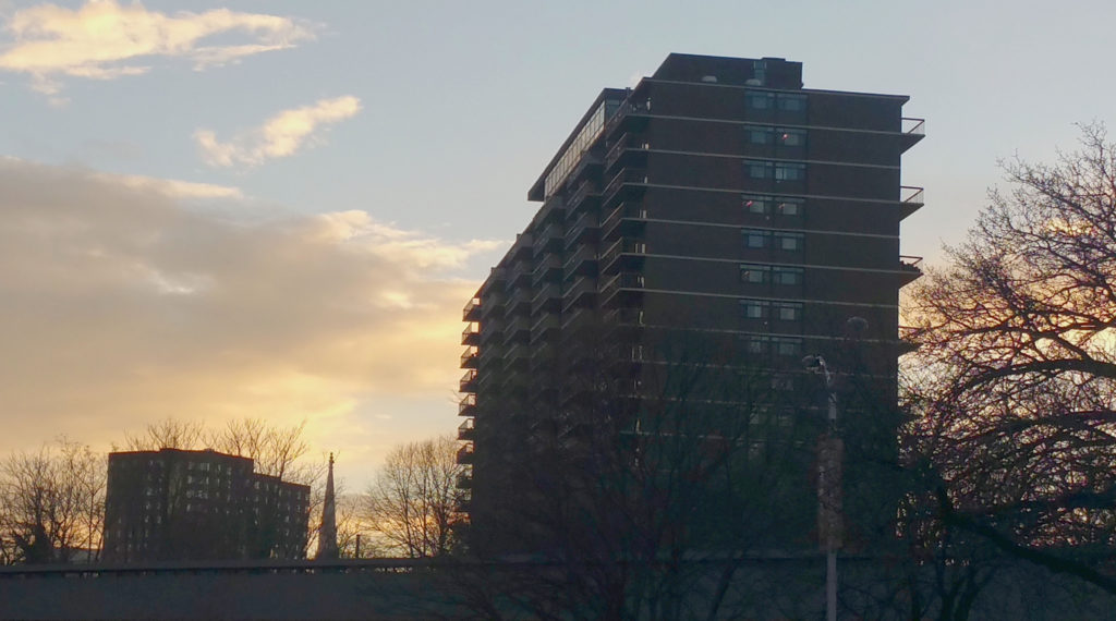 Sunset view of Bolton Hill (Baltimore, MD) featuring blue sky, white clouds and bare trees. High-rise, residential building and overpass seen in foreground; high-rise, residential building and church steeple in background.