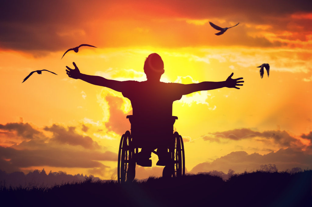 Disabled man has a hope. He is sitting on wheelchair and stretching hands at sunset.