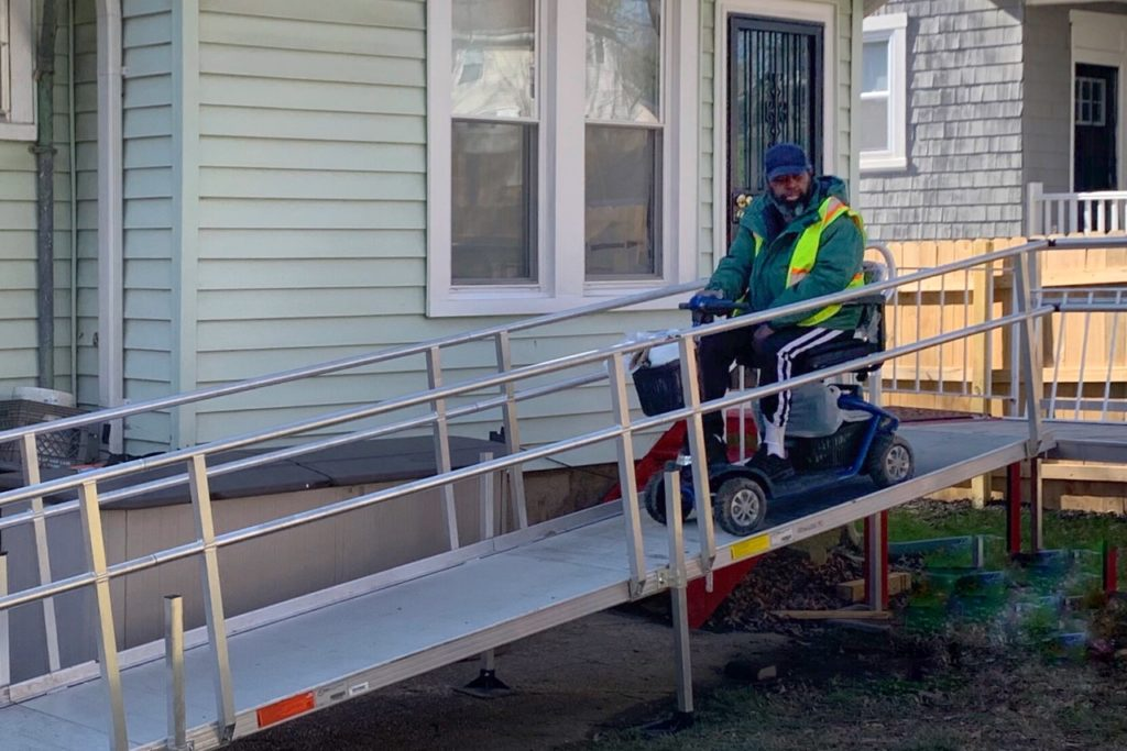 electric wheelchair using a metal ramp set up from the front door of a house