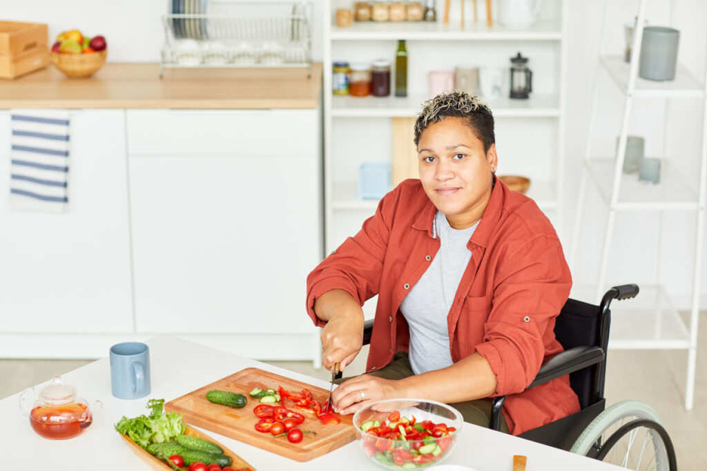 Portrait of African disabled young woman with short hair looking at camera while sitting in wheelchair and cutting vegetables in the kitchen