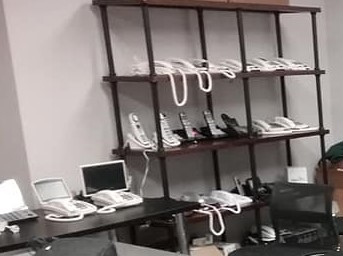 Shelf and table with a variety of telephones displayed