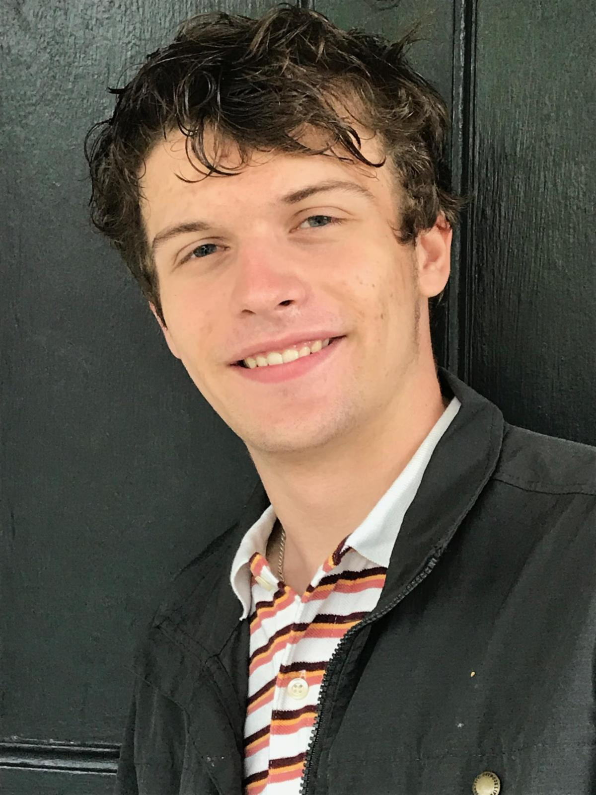 Young white man wearing a striped shirt standing in front of black background smiling